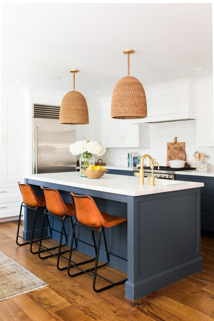 Studio McGee kitchen with blue cabinets, leather bar stools.
