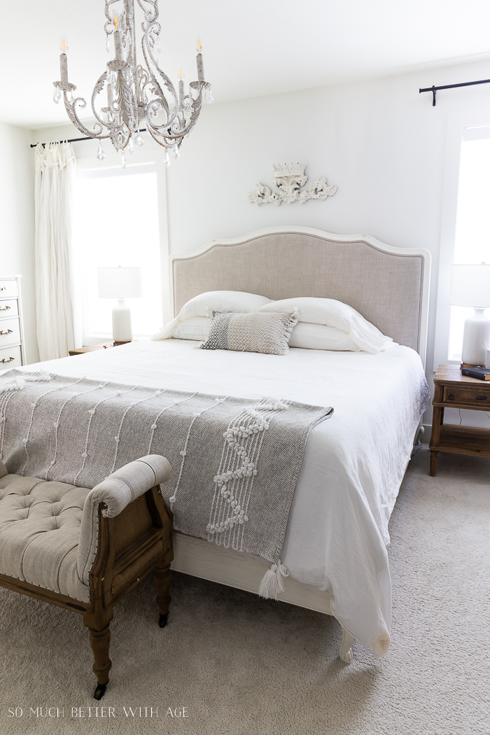 White linen bed with chandelier in bedroom.