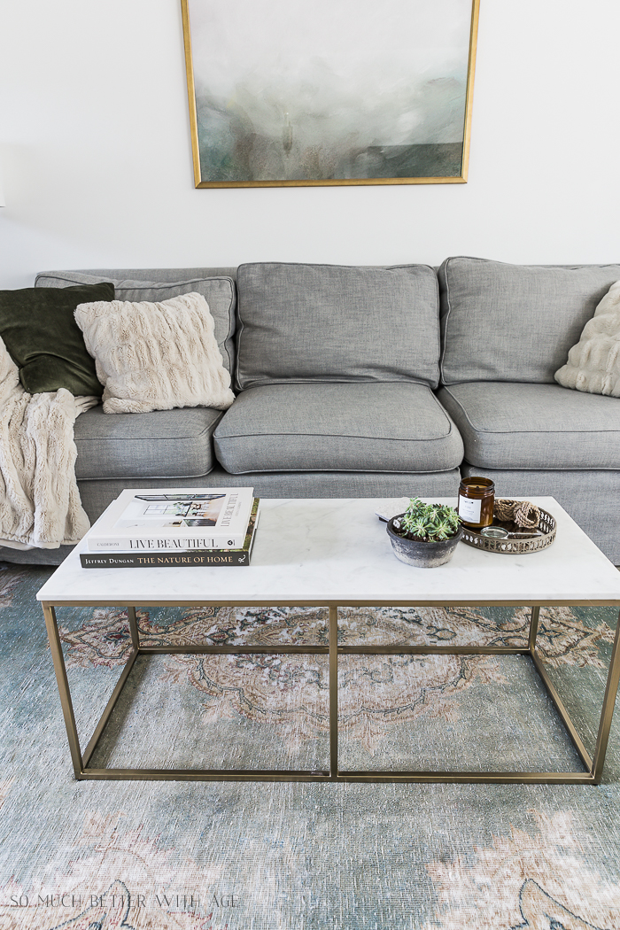 Grey couch with marble coffee table and green artwork.