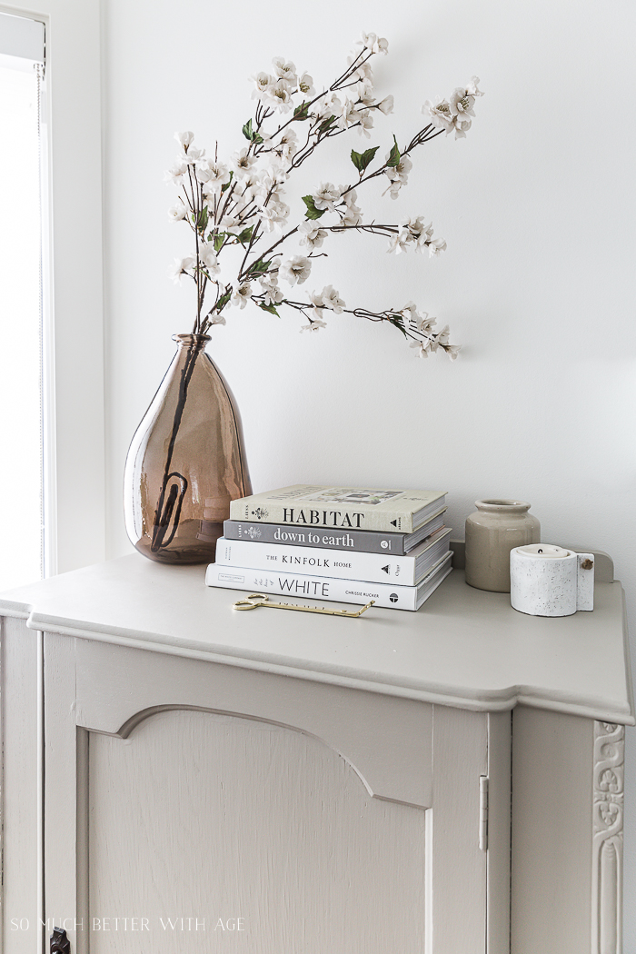 Blossom branches in brown vase and books on painted cabinet.