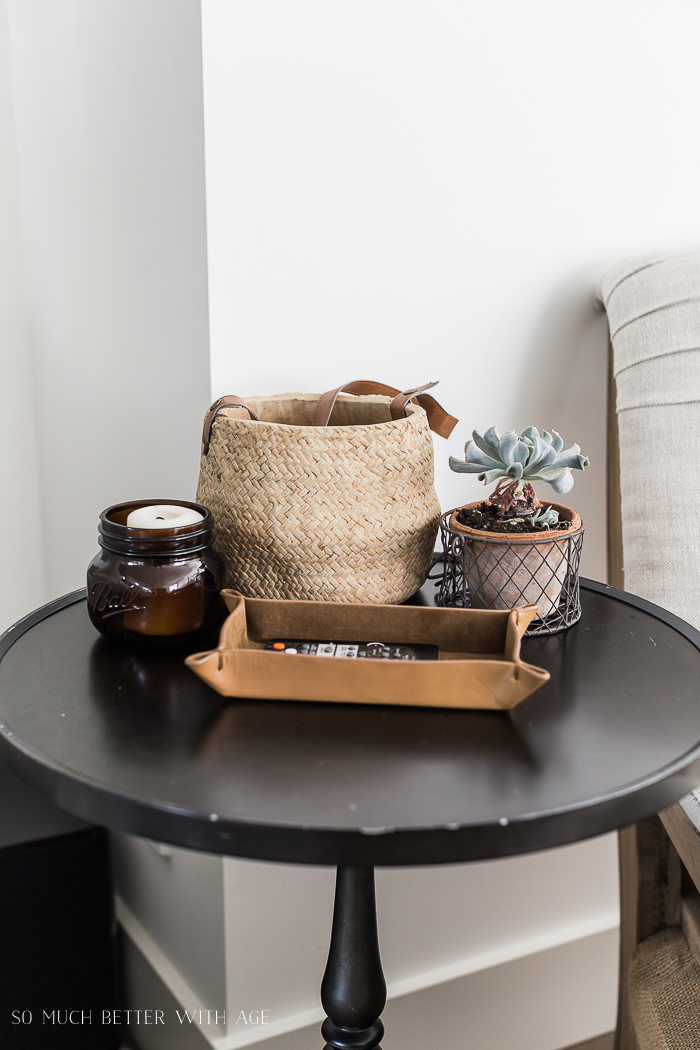 Black side table with basket planter, plant, candle.