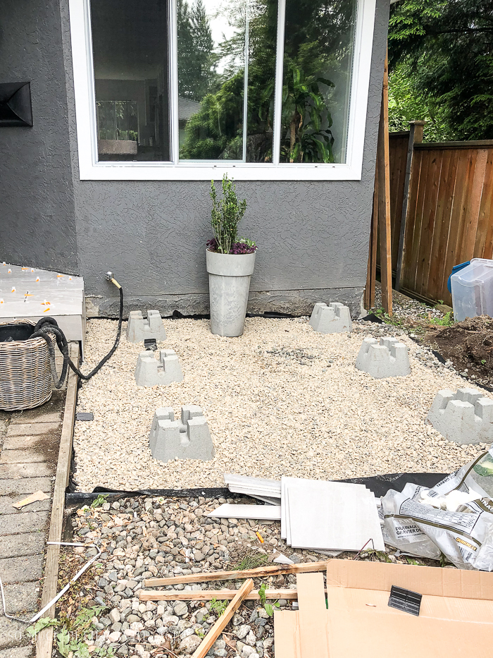 Drainage rock over landscape fabric in front of grey house in front yard.
