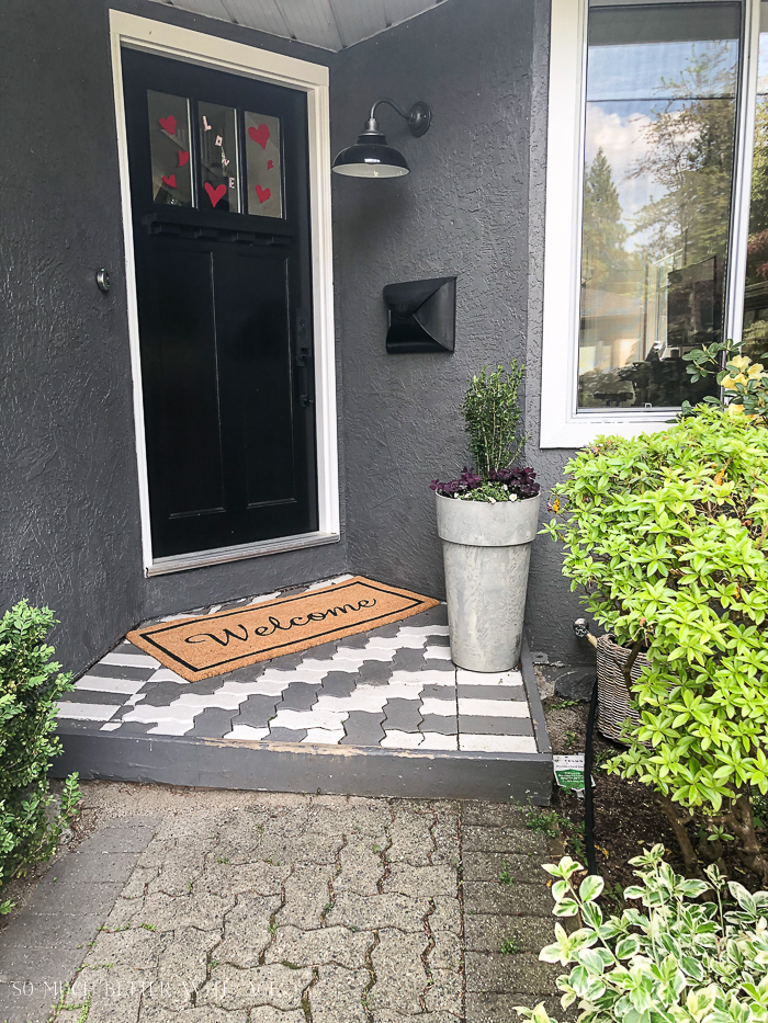 Front door area with black door and white and painted brick pavers.