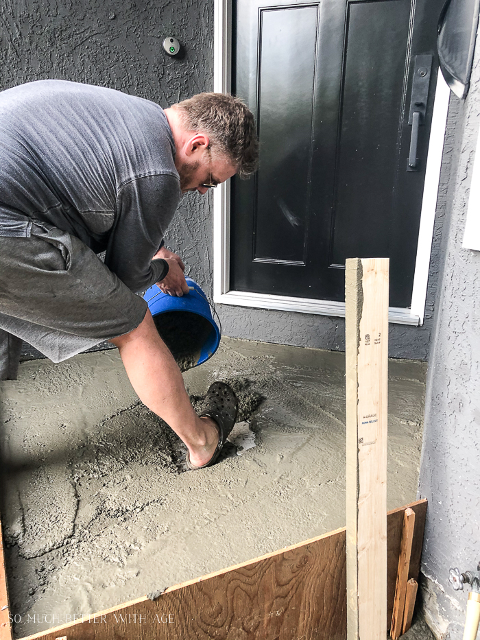 Man pouring bucket of concrete in front of house.
