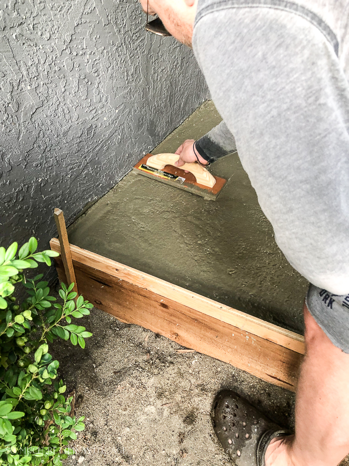 Man smoothing out concrete step.