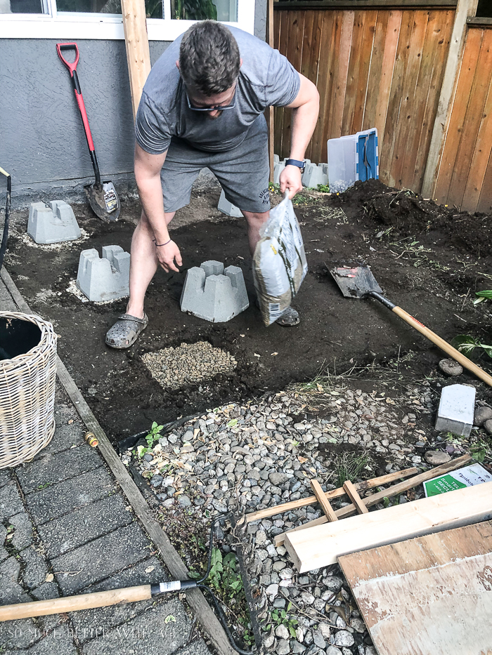 Man laying down drainage rock to build a deck.