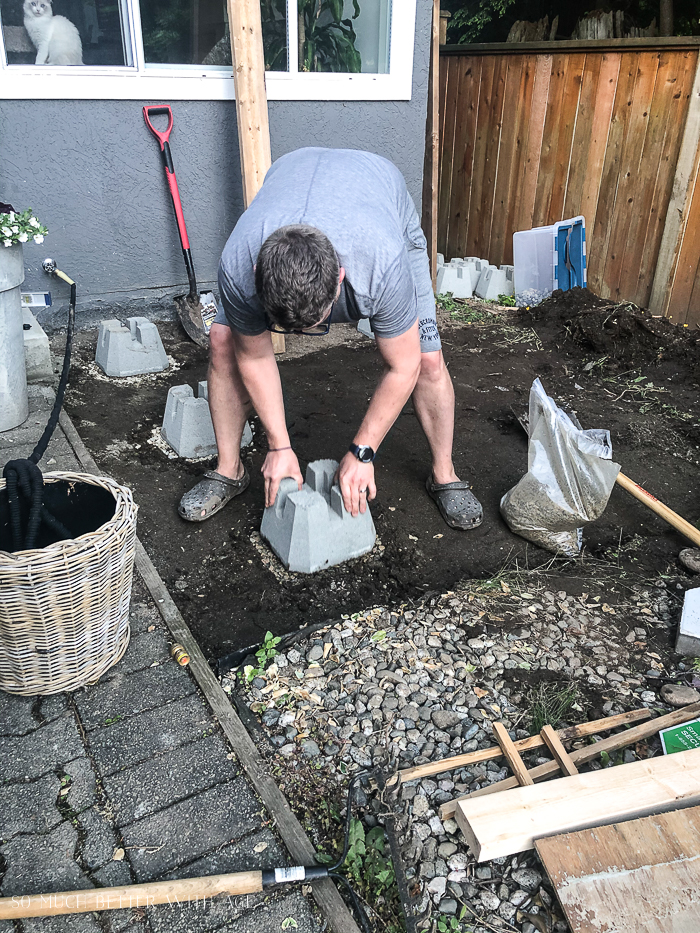 Placing decking block down preparation for building a deck.