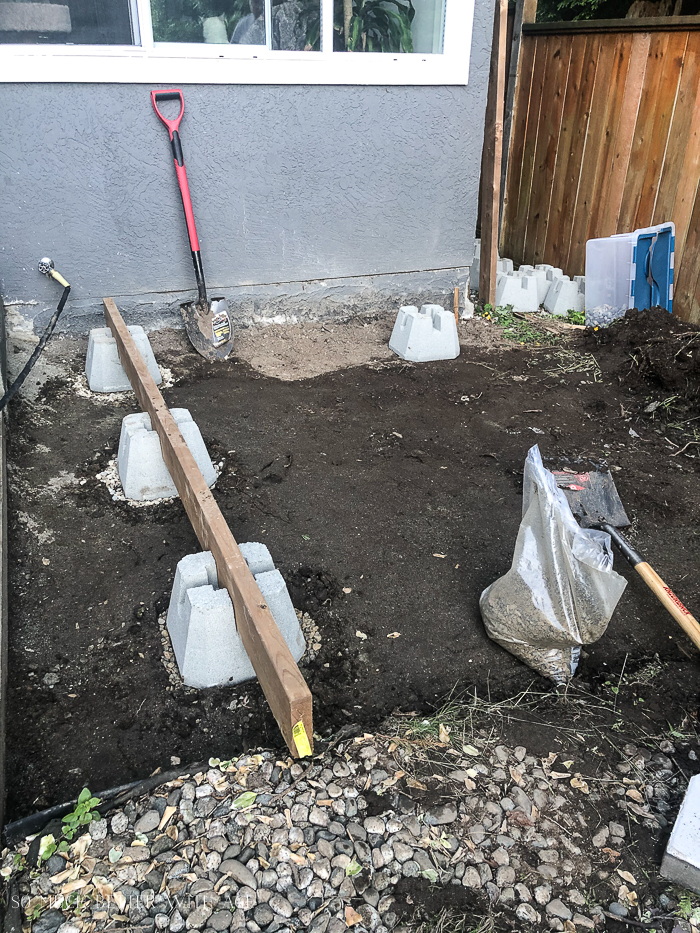 4-way deck blocks in ground in front of grey house.