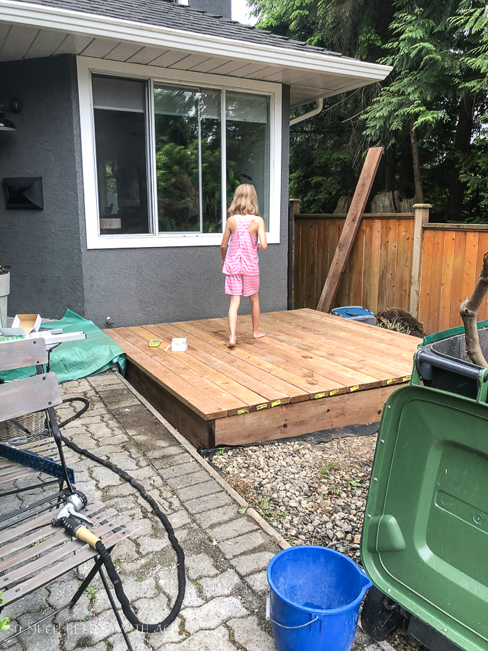Newly built deck with girl walking on it.
