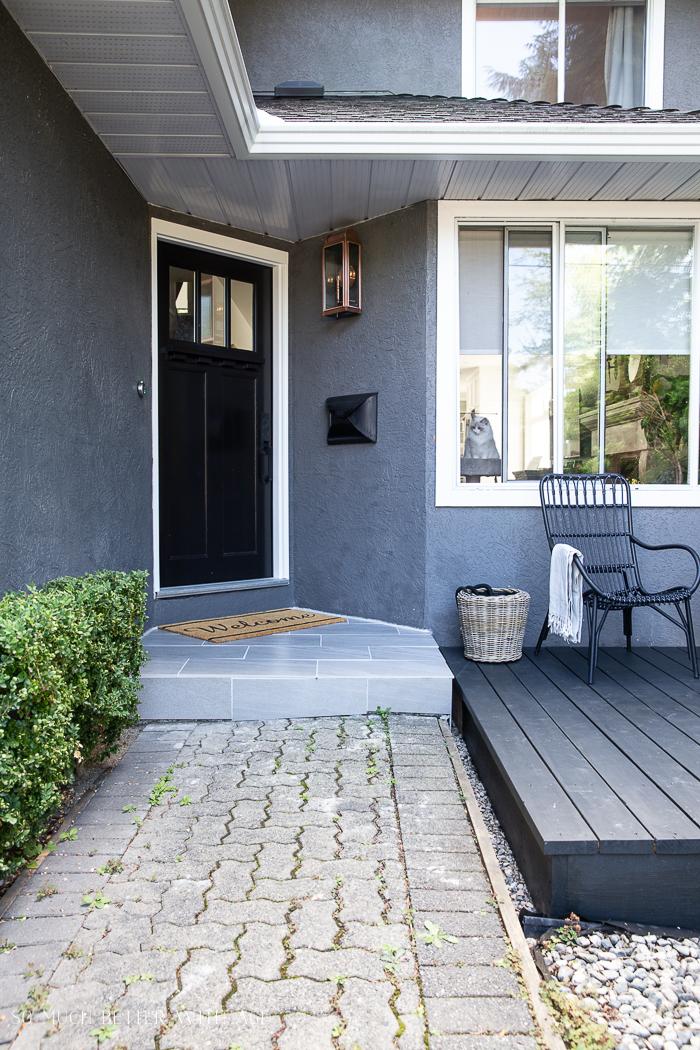 Grey house with black door and cat in window.