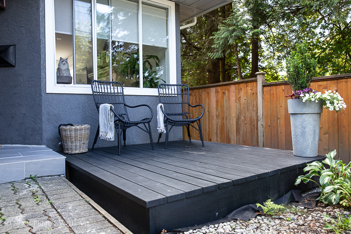 Black deck in front of grey house with two black chairs.