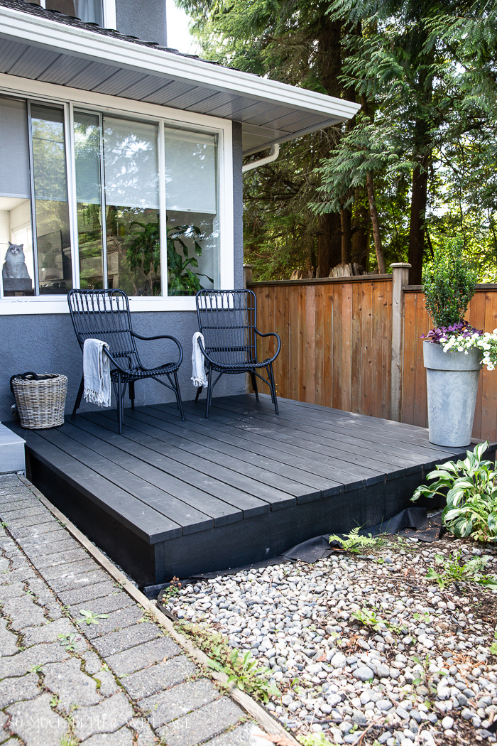 Black freestanding deck in front of grey house with cat in the window.