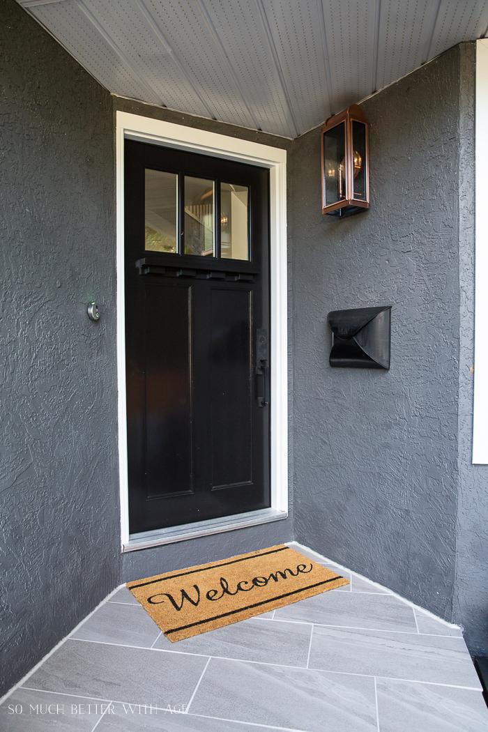 Welcome mat on front door step with black door and copper light fixture.