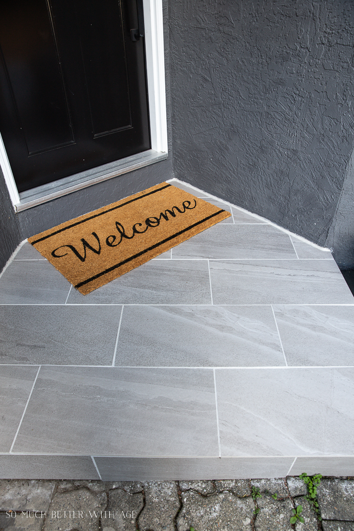 Grey tiles and white grout front door step with welcome mat.