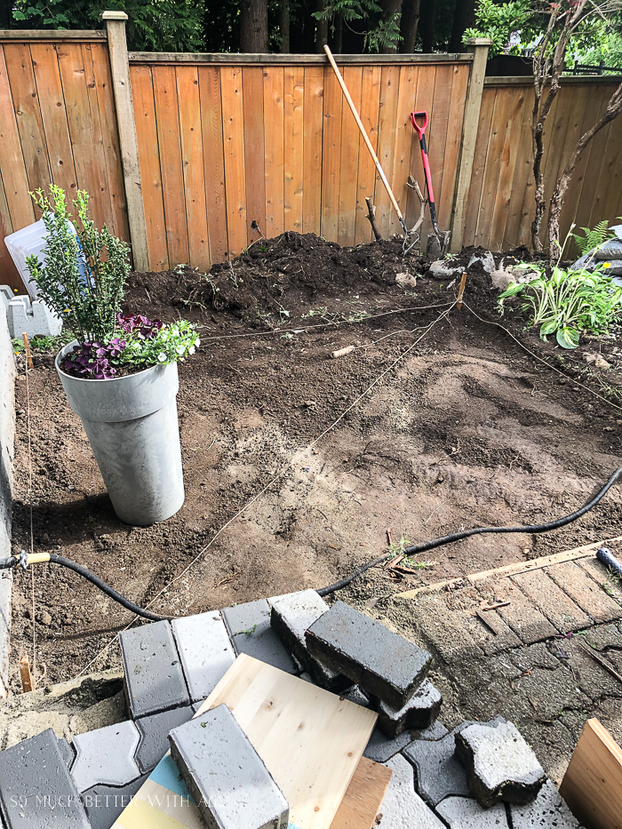 Preparing ground for a deck with string and wood stakes.