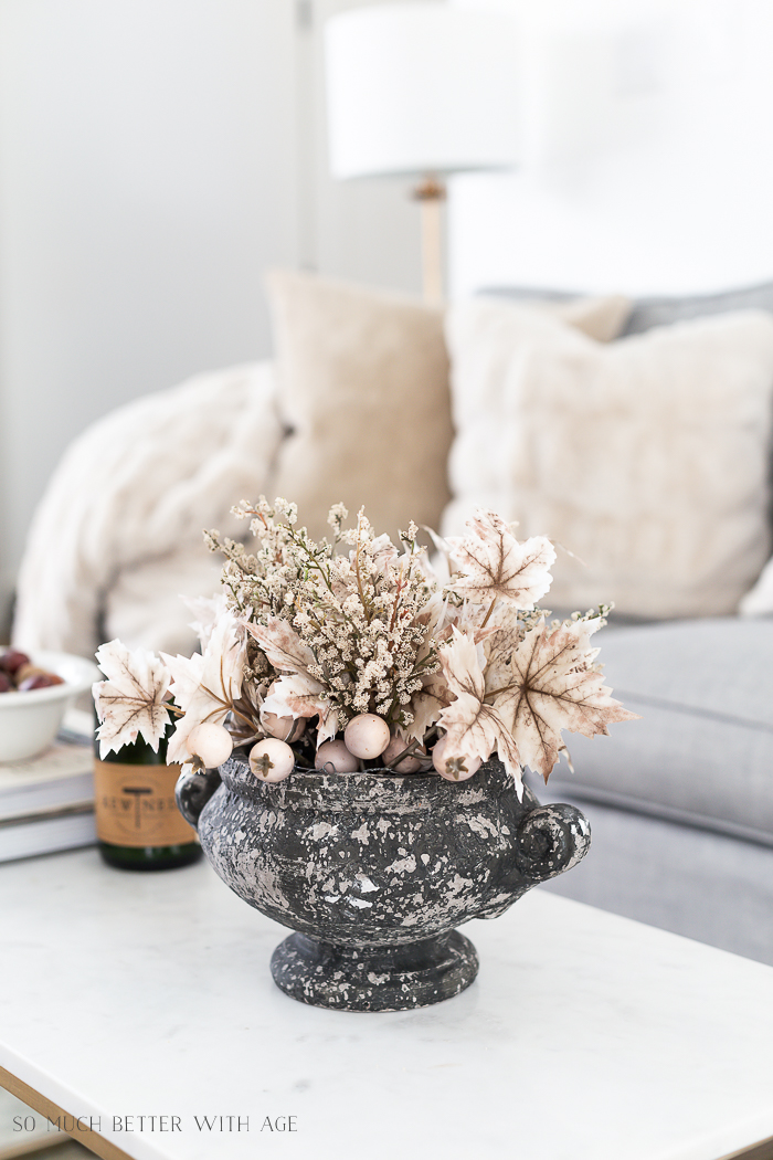 Fall leaves in planter on coffee table. Neutral decor.