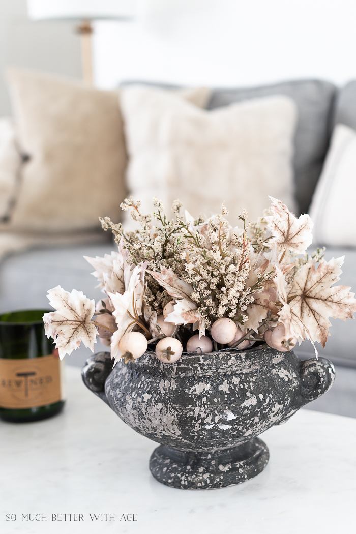 Fall leaves and neutral faux stems in grey rustic planter on coffee table.