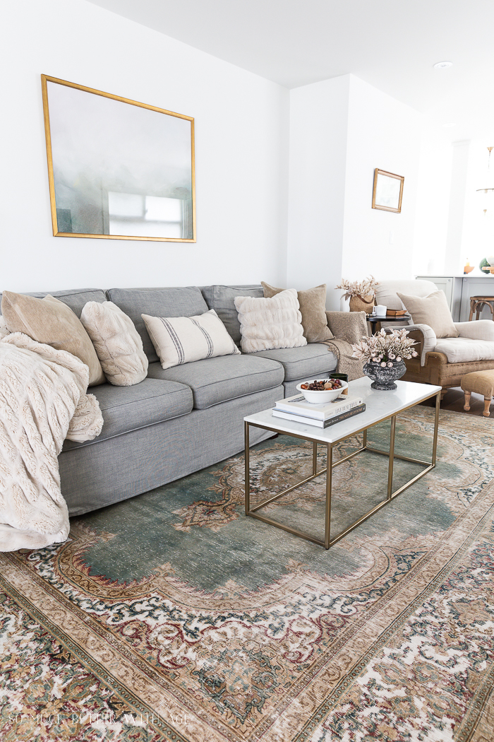 Neutral living room with cozy cream and tan pillows and green and tan rug.