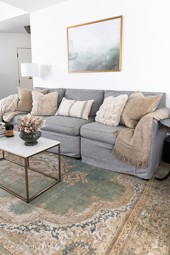Sala de estar com sofá cinza e tapete verde e castanho com arte emoldurada com moldura dourada.