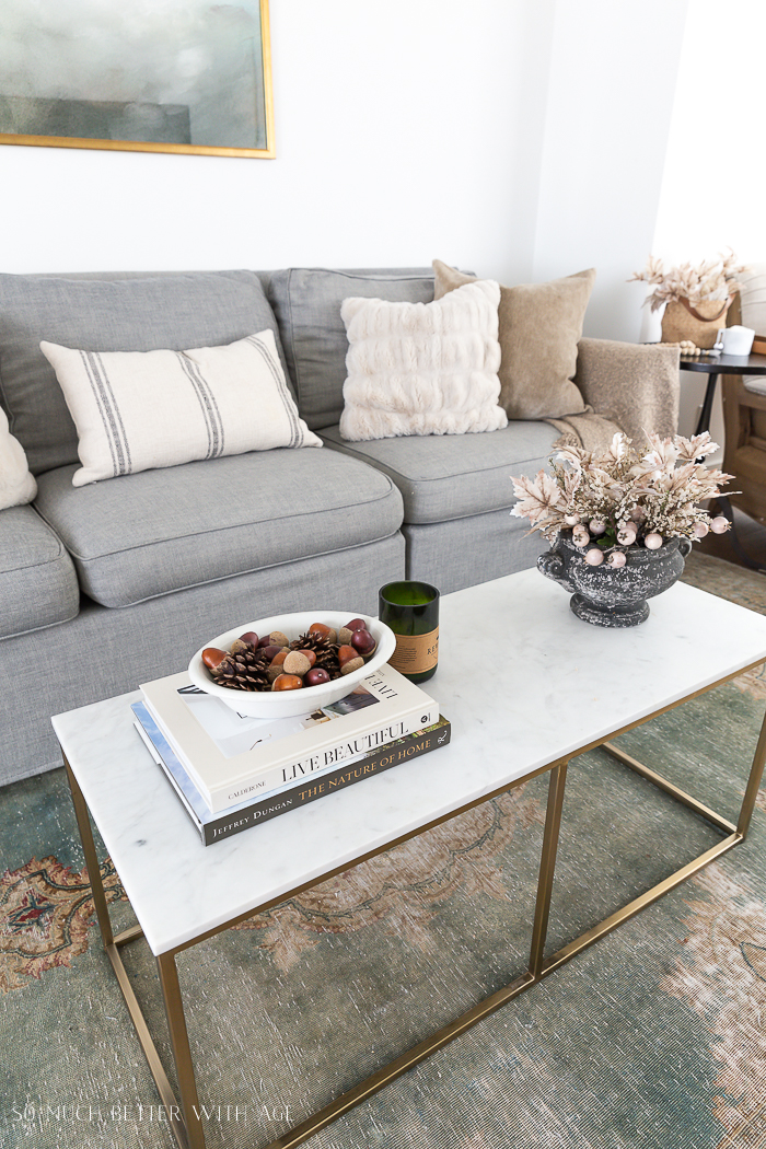 Living room grey couch with marble coffee table and fall leaves in rustic vase on coffee table.