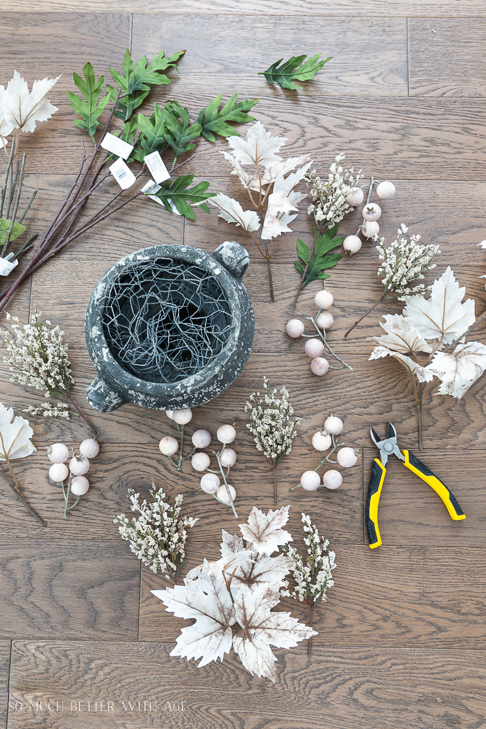 Assortment of faux or fake fall leaves on floor with wire cutters and planter with chicken wire in it.