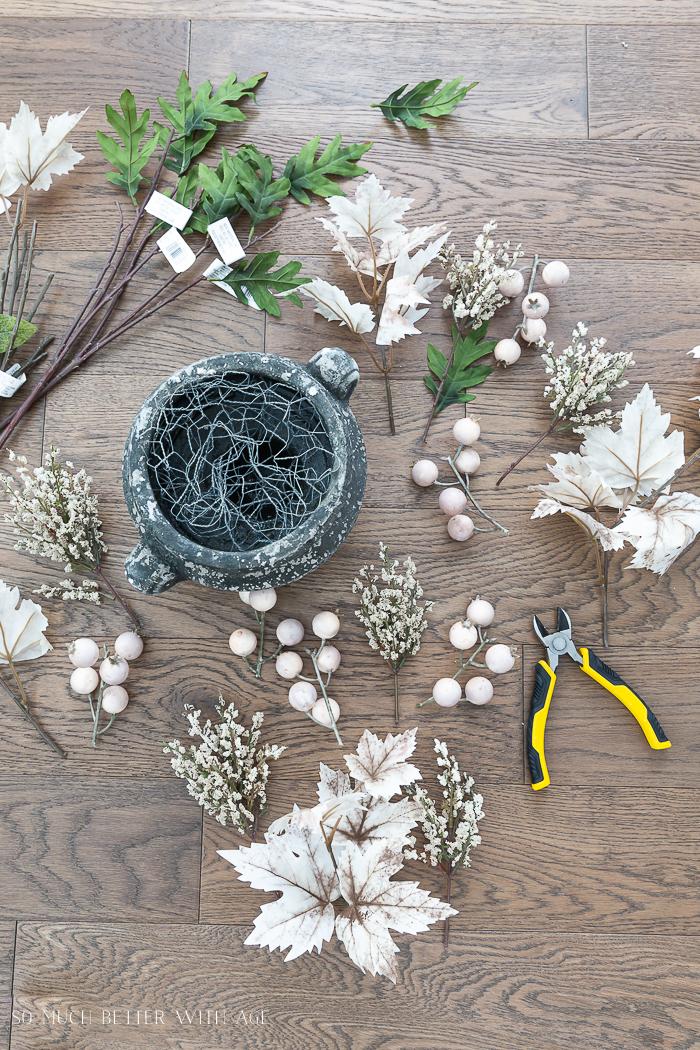Variedade de folhas caídas falsas ou falsas no chão com alicate e plantador com tela de arame.
