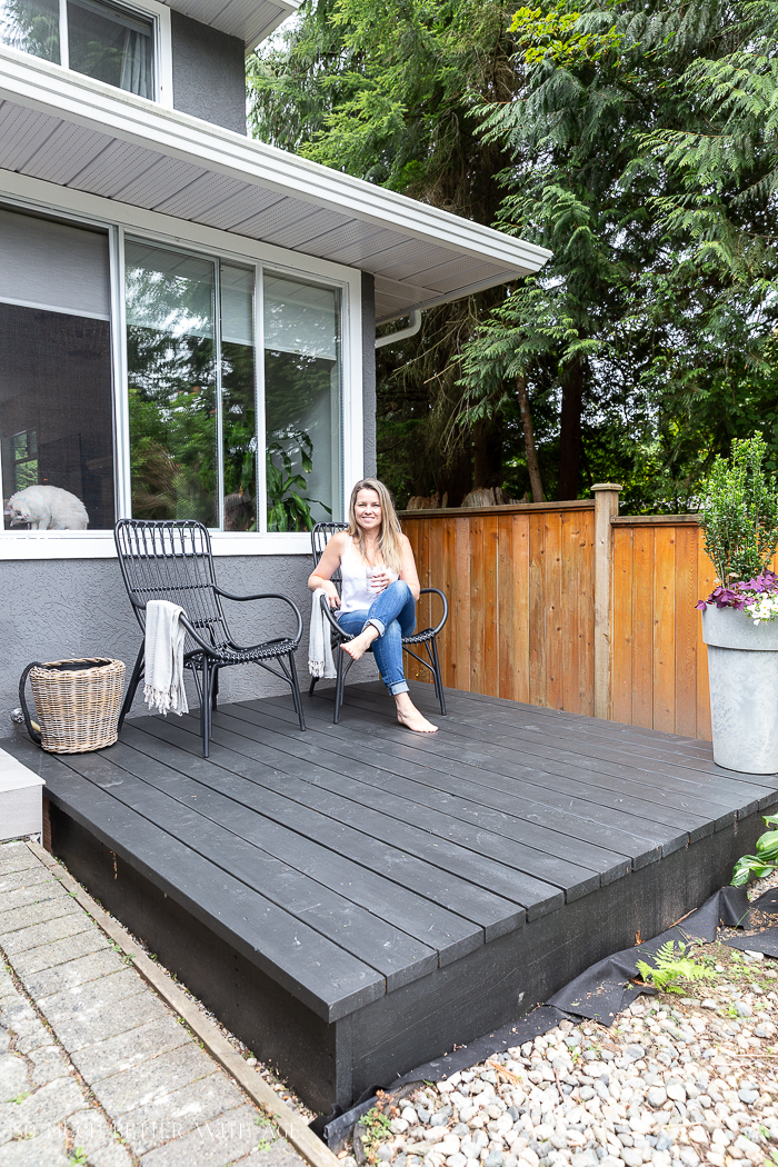 Woman sitting on black deck in front of house.
