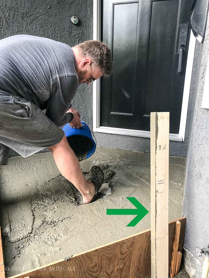 Man pouring bucket of concrete out with arrow pointing to a 2x4 for a level.