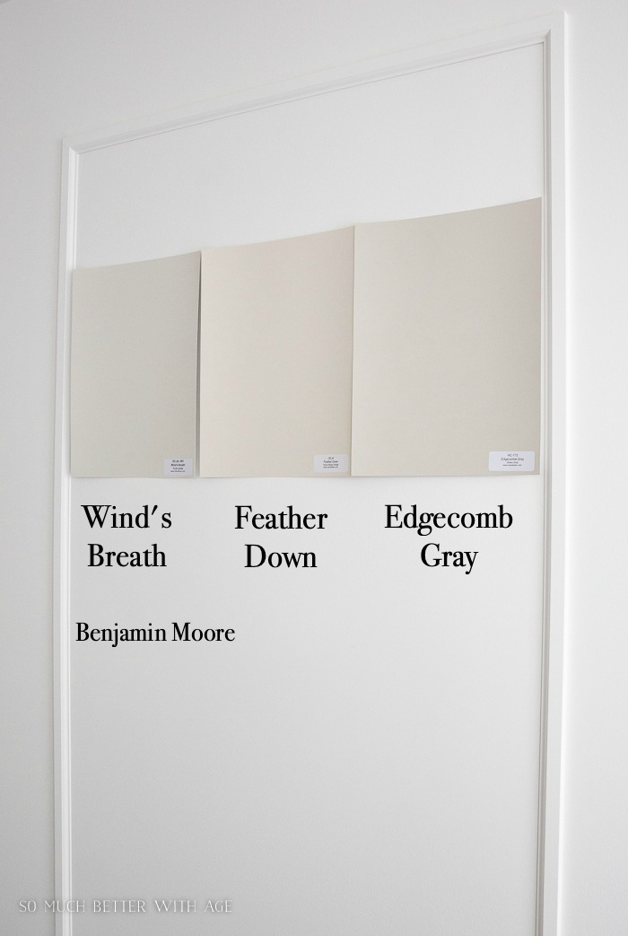 Benjamin Moore paint color samples on wall, Wind's Breath, Feather Down and Edgecomb Gray.