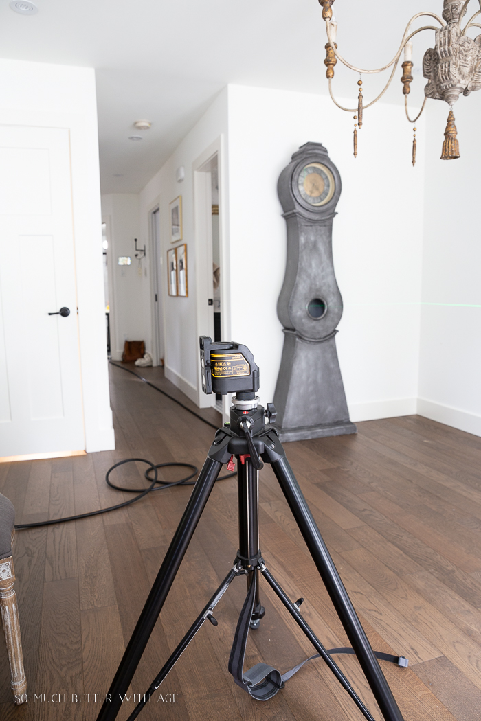 Laser level on tripod in dining room with clock in background.