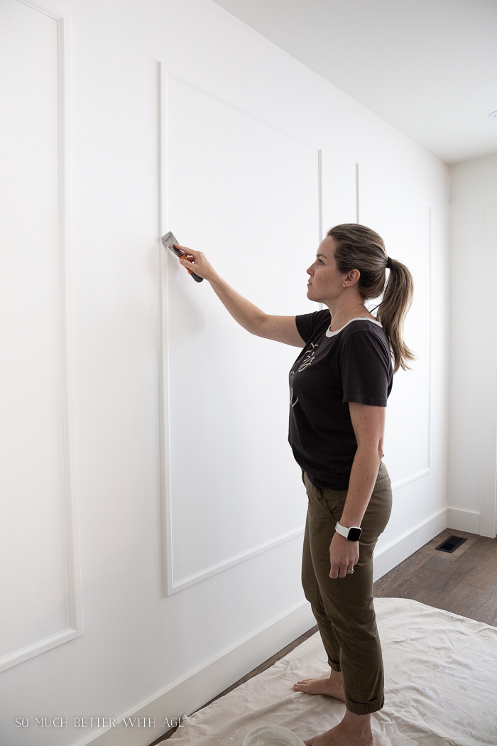 Woman filling holes on trim on wall.