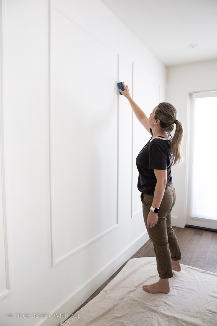 Woman sanding moulding trim on a wall.
