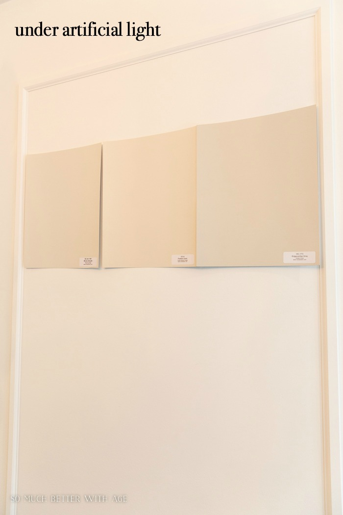Paint sample boards on wall under artificial light.