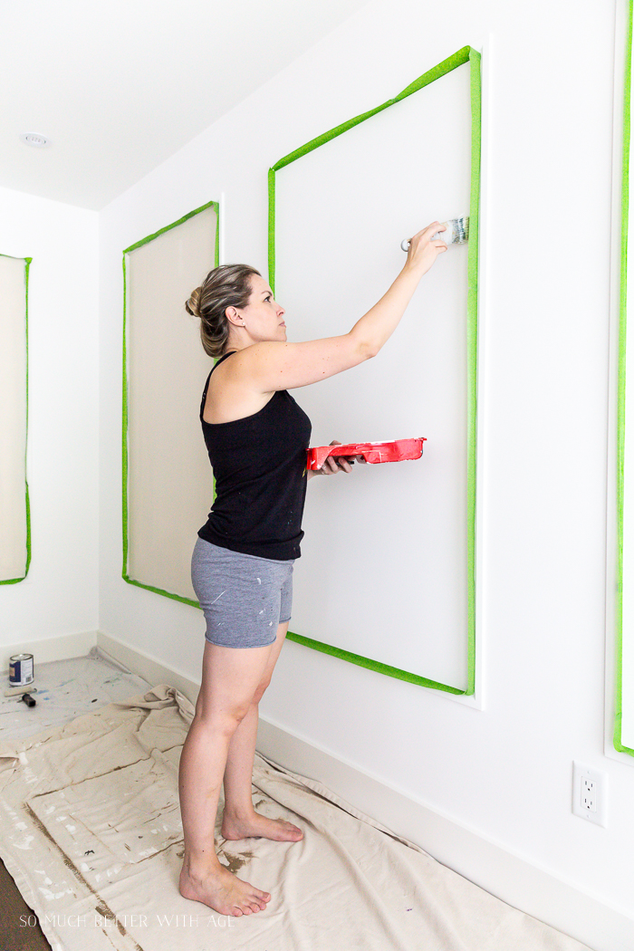 Woman painting walls and moulding.