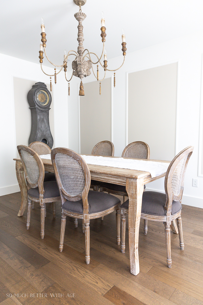 French chandelier and Mora clock and dining table with caned back chairs.