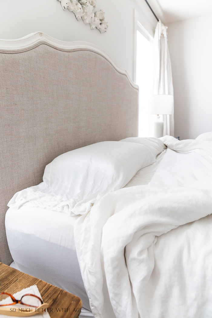 Sleeping pillows in bed with linen headboard.