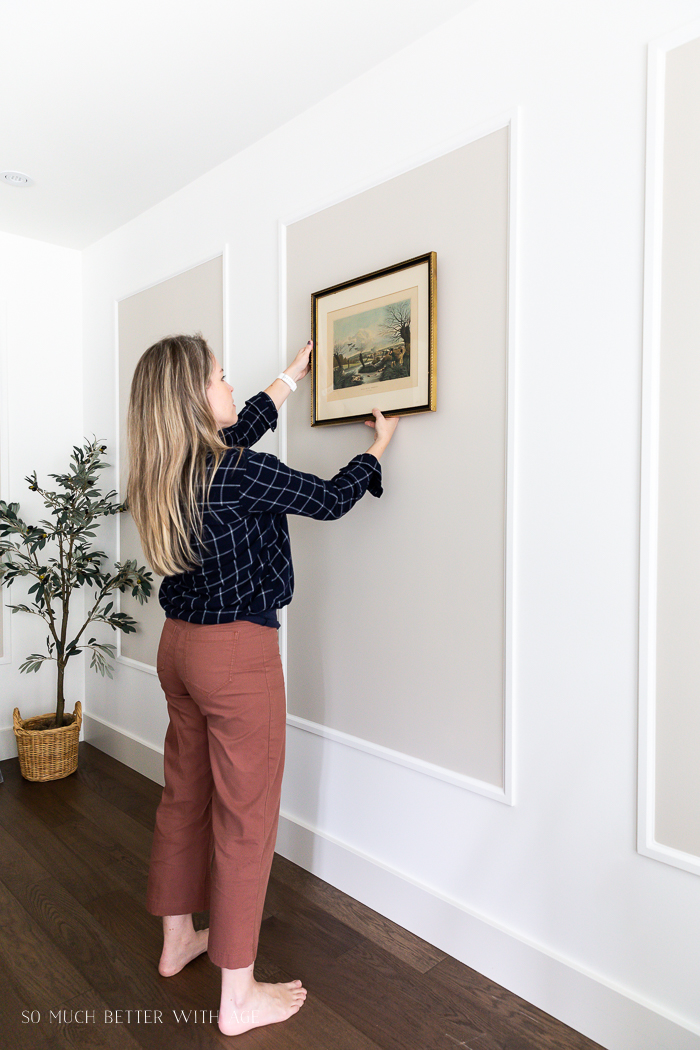 Woman hanging vintage art on wall with mouldings.