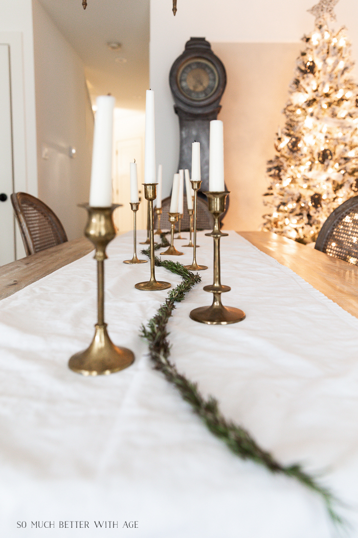 Brass candlesticks with candles on white runner with Christmas tree in background.