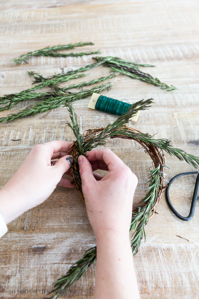 Tying rosemary to grapevine wreath.