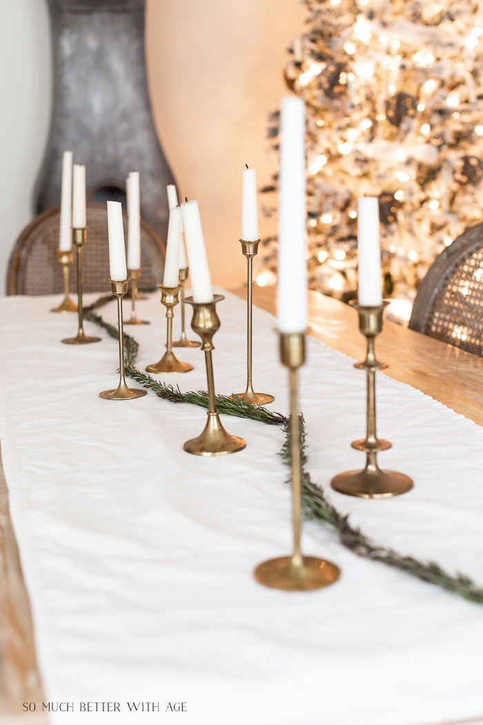 Brass candlesticks on table with Christmas tree in background.