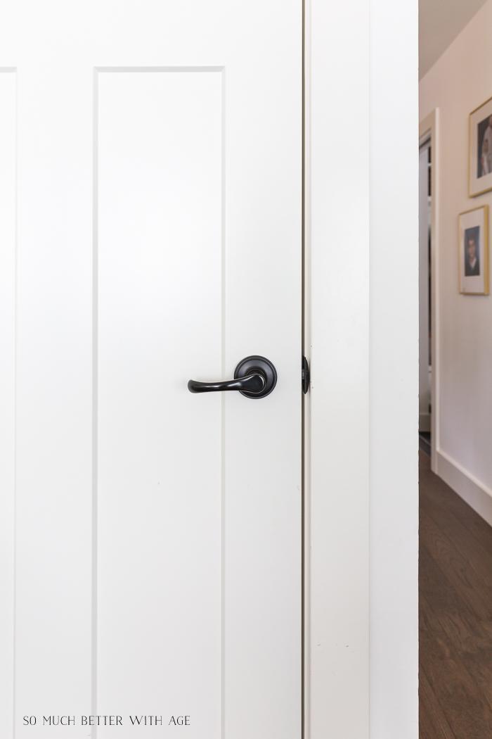 Close-up shot of black door handle on white door.