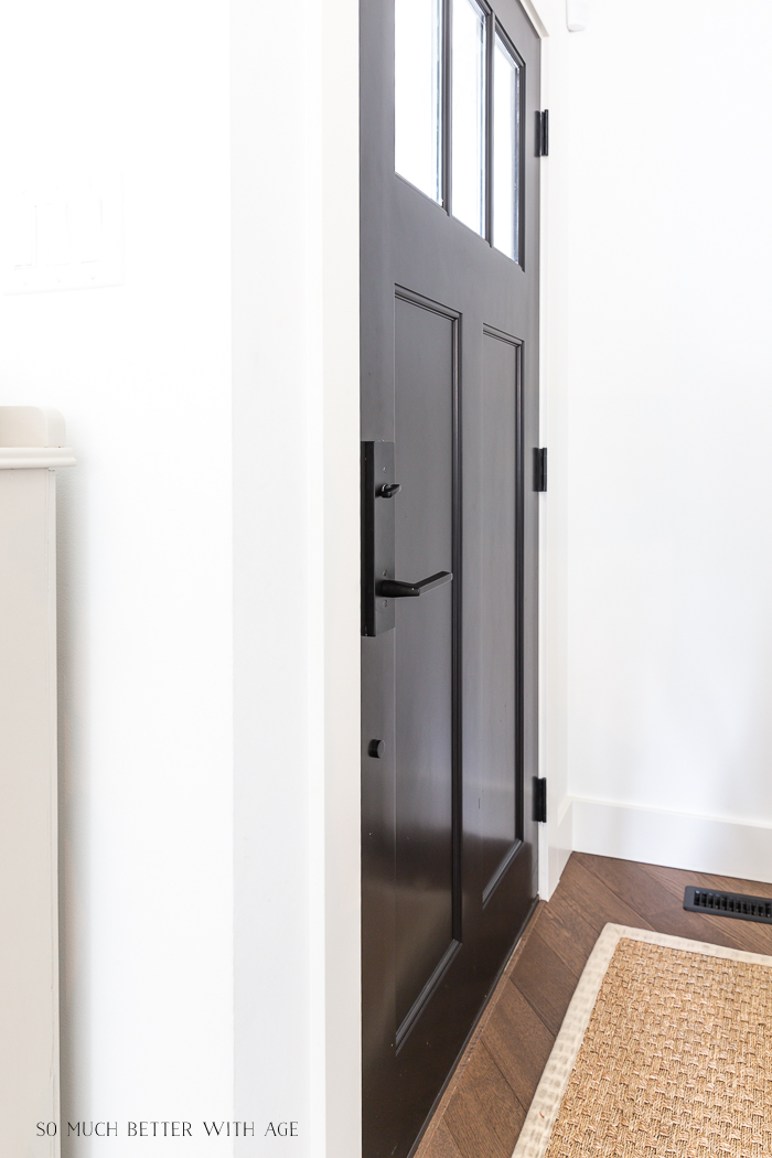 The black door and black handle with white walls around it.