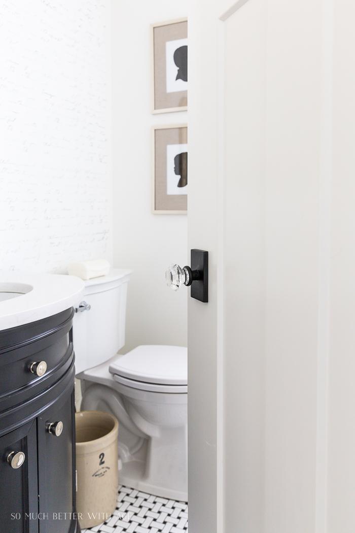Powder room with glass doorknob on white door with grey vanity.