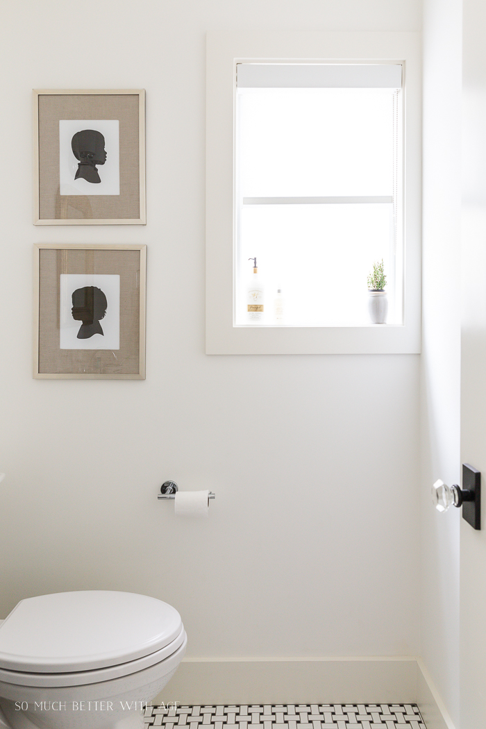 Bathroom with two framed silhouettes and black and white tile.