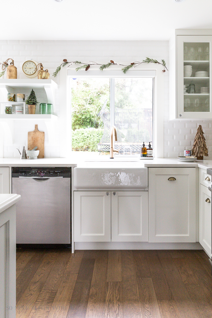 Christmas decor in a big white kitchen with farmhouse sink and big window.