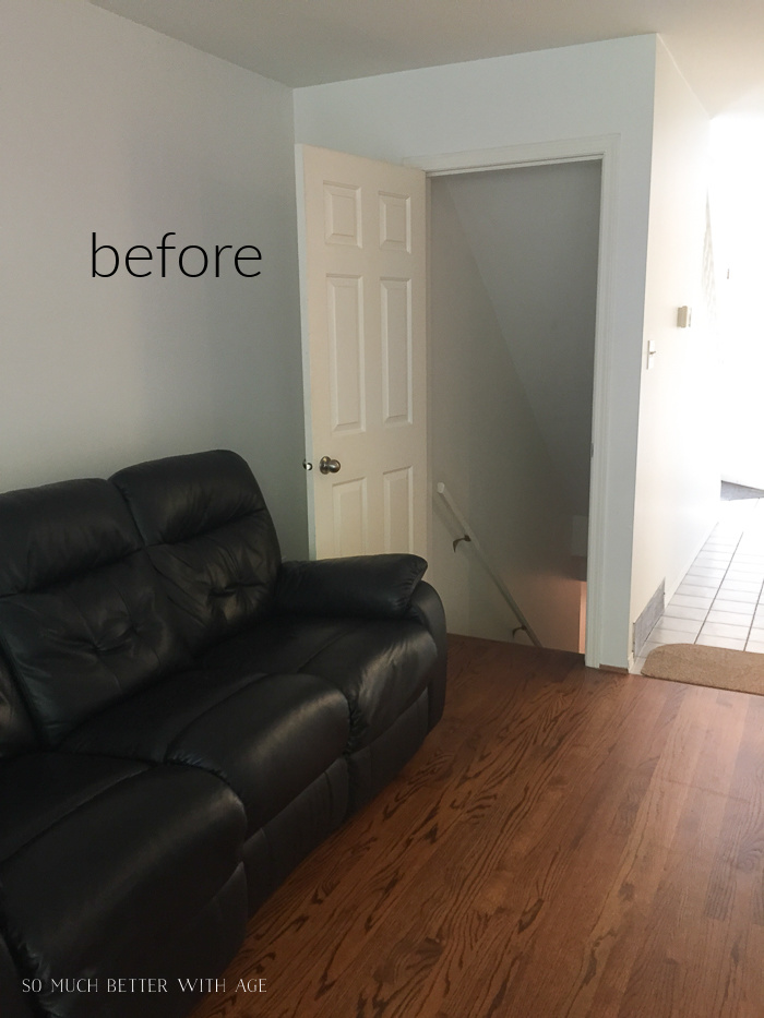 Before photo of family room with black leather sofa.
