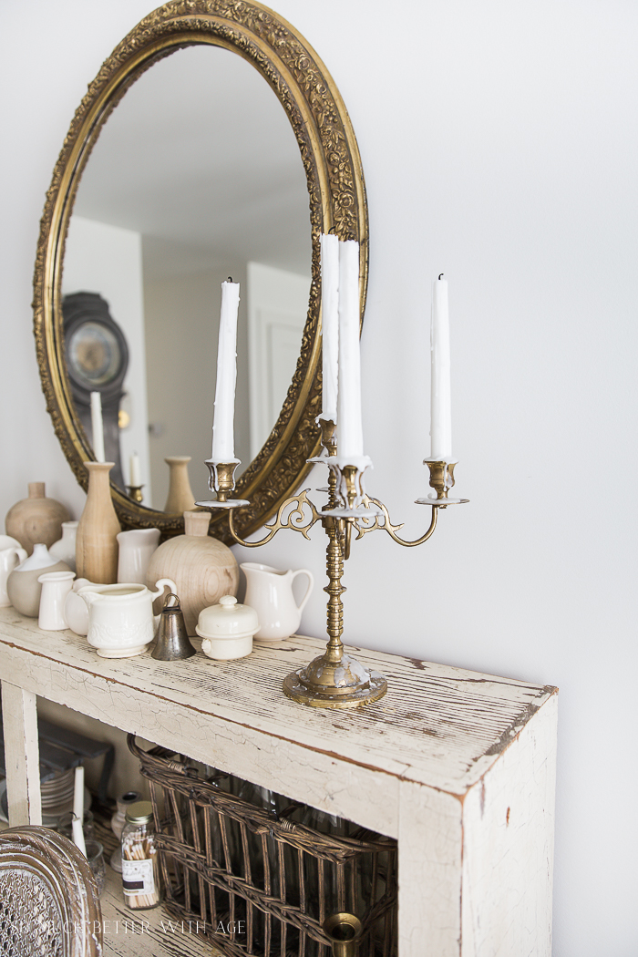 Gold mirror and candelabra on cabinet.