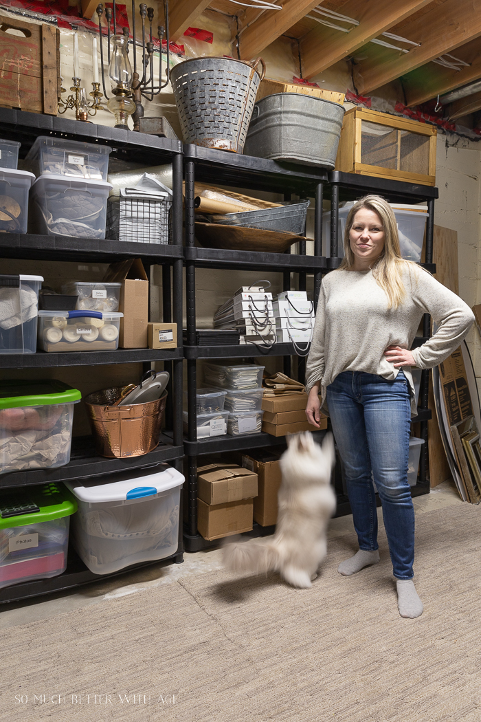 Woman and cat standing in front of basement shelves.