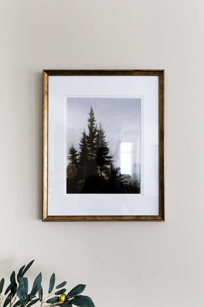 Artwork of trees framed in gold frame.