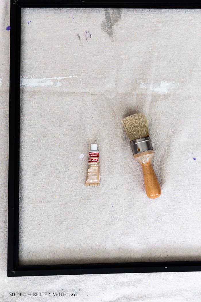 Black frame, Rub n Buff and paint brush on drop cloth.